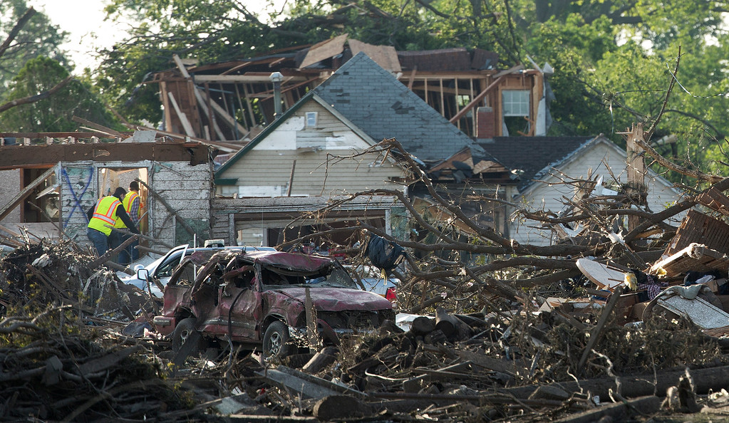 . Officials walk through the tornado damaged town of Pilger, Neb.,  on Tuesday,  June 17, 2014. The National Weather Service says the storm that struck northeast Nebraska appears to have produced four tornadoes, one of which ravaged the town of Pilger.   (AP Photo/The World-Herald, Ryan Soderlin)