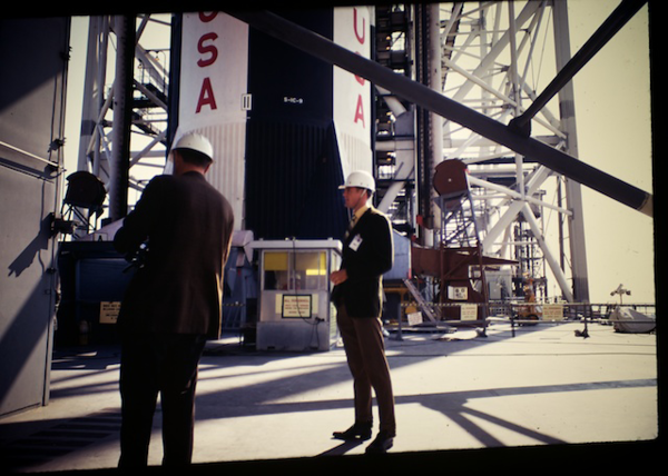 Miles Ross and son Bob waiting to ride an elevator to the top of the launch umbilical tower at pad 39A