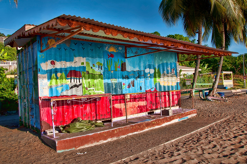 A closed refreshment stand with local scenes painted on the building.