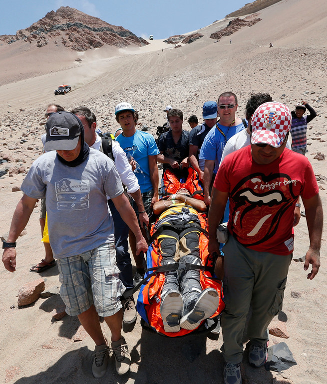 . Medics, helped by fans, evacuate Leonardo Martinez of Bolivia who was injured after crashing with his quad in the 3nd stage of the 2013 Dakar Rally from Pisco to Nazca, Peru, Monday, Jan. 7, 2013. The race finishes in Santiago, Chile, on Jan. 20. (AP Photo/Victor R. Caivano)