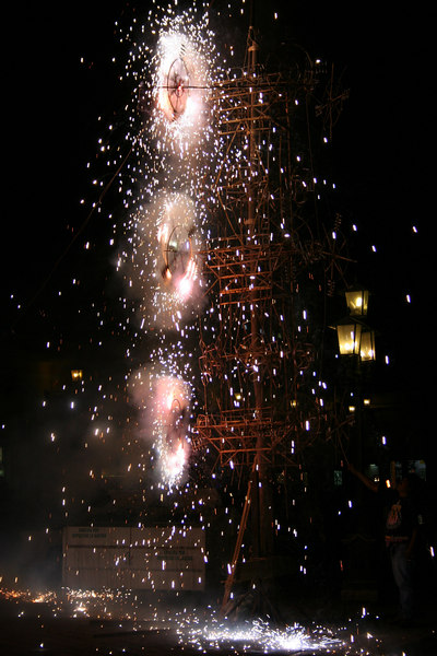 "fireworks in front of a church.. they call it the ""burning of the castle.""  it's being burned to mark the start of a 3 day walk to a saint statue in another town.  some people are there with bags on there backs."