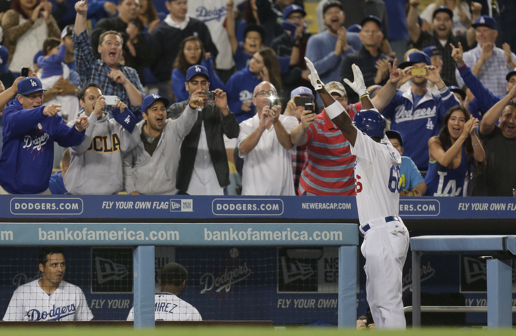 . Los Angeles Dodgers Yasiel Puig, right, acknowledges the crowd after he homered during the sixth inning of their baseball game against the San Diego Padres, Tuesday, June 4, 2013, in Los Angeles. (AP Photo/Jason Redmond)