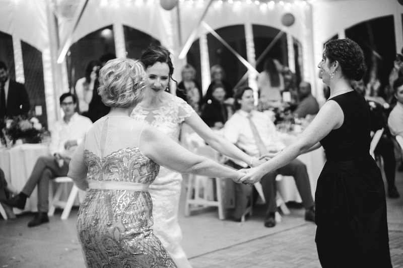 The bride, her sister, and mother hold hands and dance in a circle to the bagpipes.
