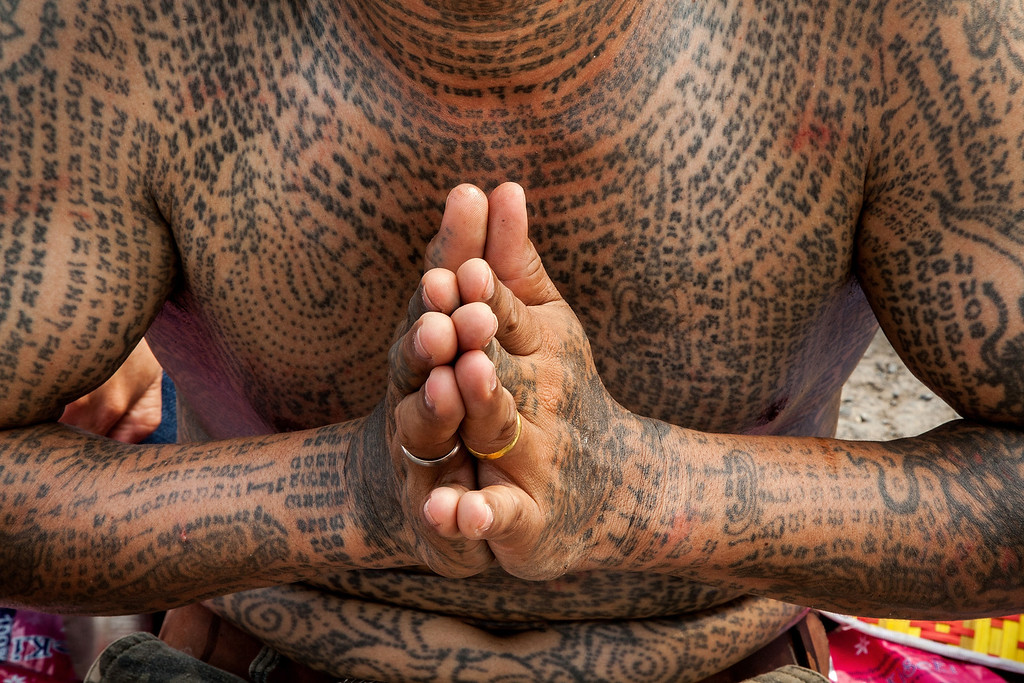 . A tattooed Thai devotee prays during the celebration of the annual Tattoo festival at Wat Bang Phra on March 15, 2014 in Nakhon Pathom, Thailand.  Thousands of believers from all over Thailand come to take part in one of the country\'s most bizarre festivals about 50 miles outside Bangkok to pay respect to the temple\'s monks who are master tattooist. In Thai culture the tattoo is worn as a symbol of spiritual and physical protection, many believe that the tattoo has mystical powers. Many tattoo fanatics choose to have monkeys and tigers as well as the Khmer/Cambodia ancient script on their bodies. (Photo by Omar Havana/Getty Images)