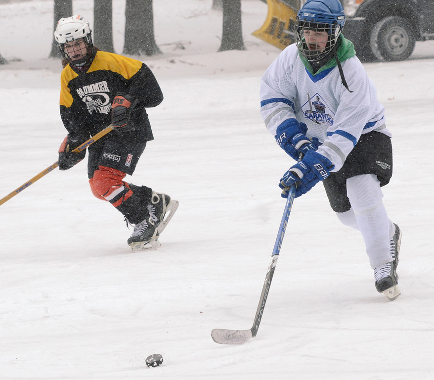 . Ed Burke - The Saratogian 01/25/14 Former Blue Streak hockey player Chad Kelly, playing for team TCGU (This Could Get Ugly) is shadowed by Becky Jaiven of Schenectady of team Lucky Puck Saturday during the Saratoga Frozen Springs Classic Hockey Tournament at Saratoga Spa State Park.