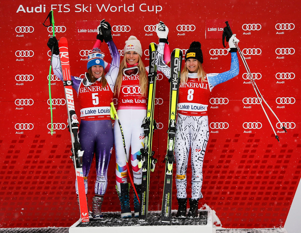 . Lindsey Vonn, center, of the United States, celebrates her first place finish on the podium with teammate and second-place finisher Stacey Cook, left, and third-place finisher and teammate Julia Mancuso following the women\'s World Cup downhill ski race in Lake Louise, Alberta, Saturday, Dec. 6, 2014. (AP Photo/The Canadian Press, Jeff McIntosh)