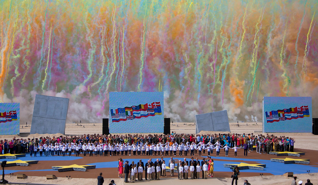 . Colored smoke fills the sky as WWII veterans stand to attention flanked by children during an international ceremony marking the 70th anniversary of the Allied landings on D-Day on Sword Beach in Ouistreham, in Normandy, France, Friday, June 6 June 2014. World leaders and veterans gathered by the beaches of Normandy on Friday to mark the 70th anniversary of World War Two\'s D-Day landings. (AP Photo/Ian Langsdon, Pool)