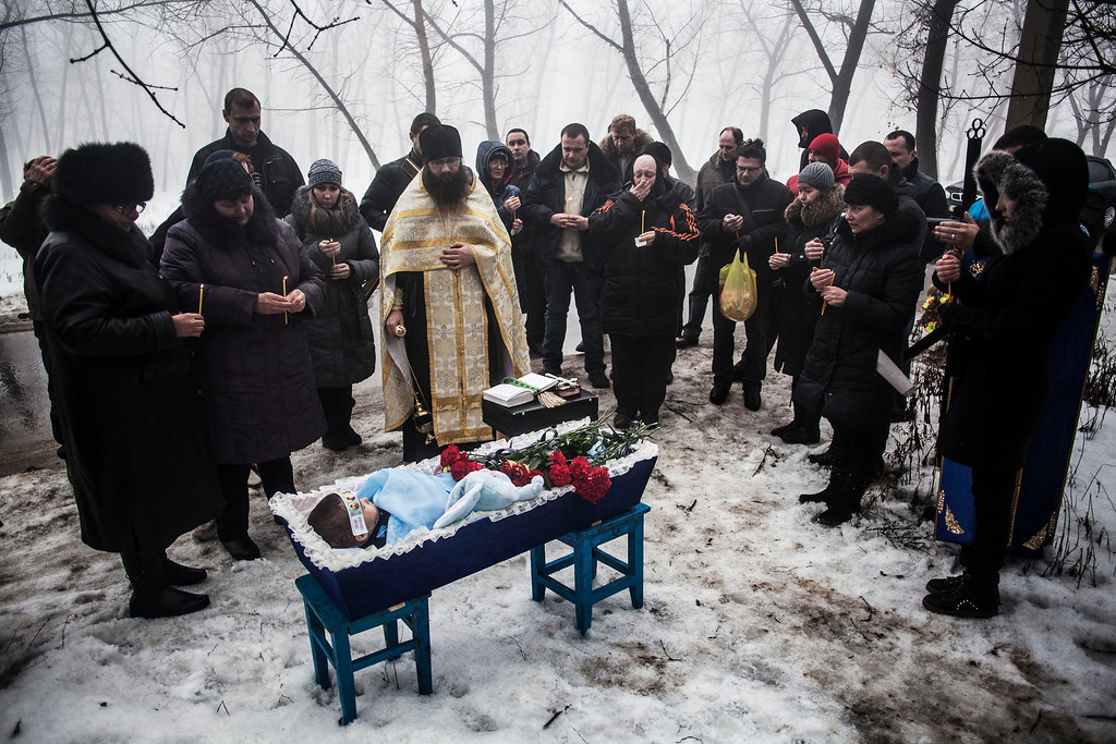 . Mourners gather around a coffin bearing Artiam, 4, who was killed in a Ukrainian army artillery strike, during his funeral in Kuivisevsky district on the outskirts of Donetsk, eastern Ukraine, Tuesday, Jan. 20, 2015. At least three civilians were killed in shelling Tuesday in eastern Ukraine as fighting continued between government and rebel forces in the separatist-held city of Donetsk. (AP Photo/Manu Brabo)