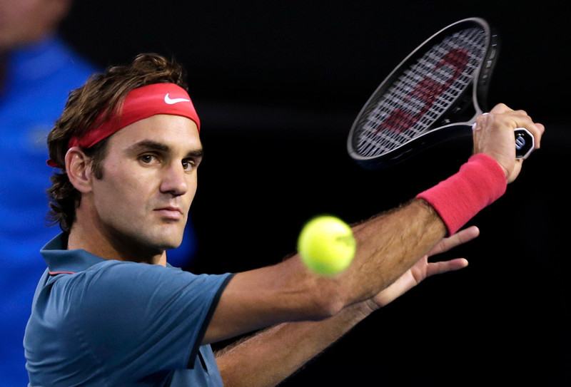 . Roger Federer of Switzerland makes a backhand return to Rafael Nadal of Spain during their semifinal at the Australian Open tennis championship in Melbourne, Australia, Friday, Jan. 24, 2014.(AP Photo/Rick Rycroft)