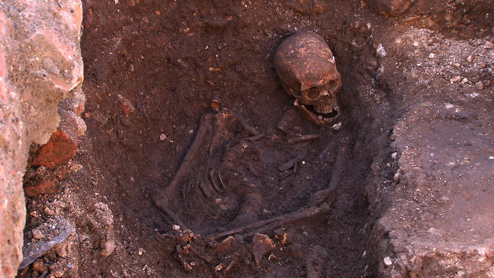Description of . The skeleton of Richard III is seen in a trench at the Grey Friars excavation site in Leicester, central England, in this picture provided by the University of Leicester and received in London on February 4, 2013. A skeleton with a cleaved skull and a curved spine entombed under a car park is that of Richard III, scientific tests confirmed, solving a 500-year-old mystery about the final resting place of the last English king to die in battle.  REUTERS/University of Leicester/Handout