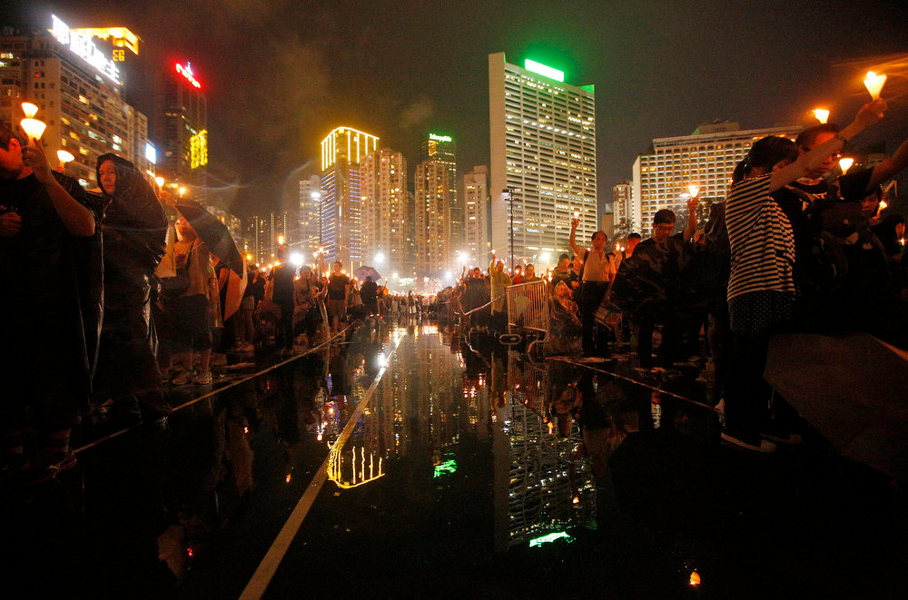 . Tens of thousands of people attend a candlelight vigil under heavy rain at Hong Kong\'s Victoria Park in Hong Kong Tuesday June 4, 2013 to mark the 24th anniversary of the June 4th Chinese military crackdown on the pro-democracy movement in Beijing. (AP Photo/Vincent Yu)