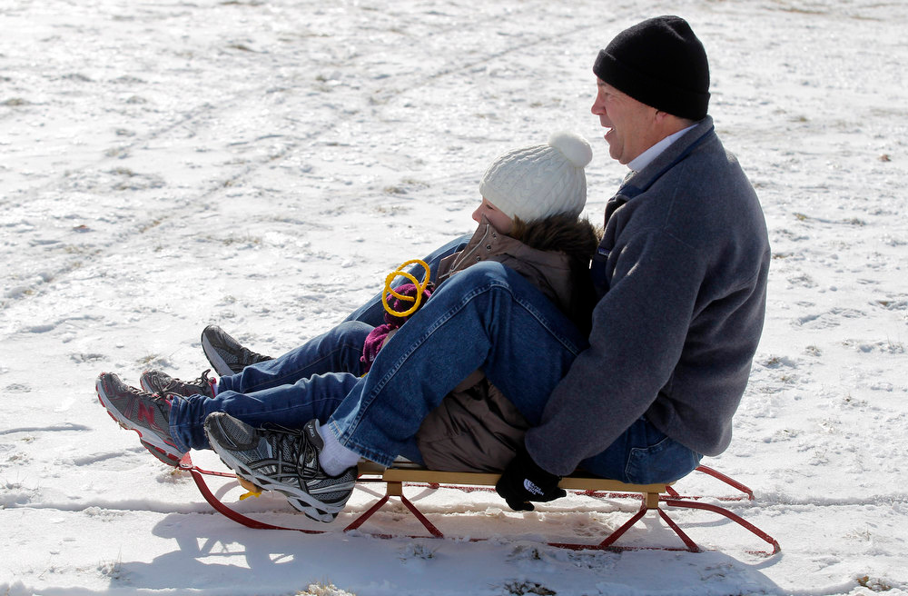 Description of . Riley Waddell, 8, of McKinney, and her grandfather Doug Batchelor, of Fort Worth, make use of the sled she got for Christmas on a hill at Foster Park, Wednesday, Dec. 26, 2012, after winter weather covered the area with layer of snow on Christmas Day. (AP Photo/The Fort Worth Star-Telegram, Rodger Mallison