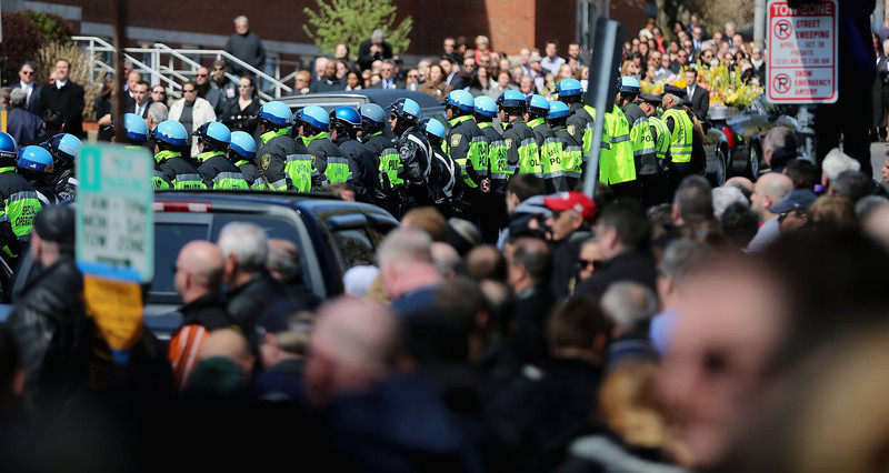 . Police officers and others gather outside the funeral for 29-year-old Krystle Campbell, who was one of three people killed in the Boston Marathon bombings, on April 22, 2013 in Medford, Massachusetts. The 29-year-old restaurant manager was raised in Medford. Massachusetts Gov. Deval Patrick has asked residents to observe a moment of silence at the time of the first explosion at 2:50 p.m. this afternoon.  (Photo by Mario Tama/Getty Images)