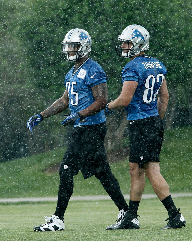 . Detroit Lions tight ends Eric Ebron (85) and Jordan Thompson (82) work out in the rain during the final day of minicamp Thursday, June 12, 2014, in Allen Park, Mich. (AP Photo/Duane Burleson)
