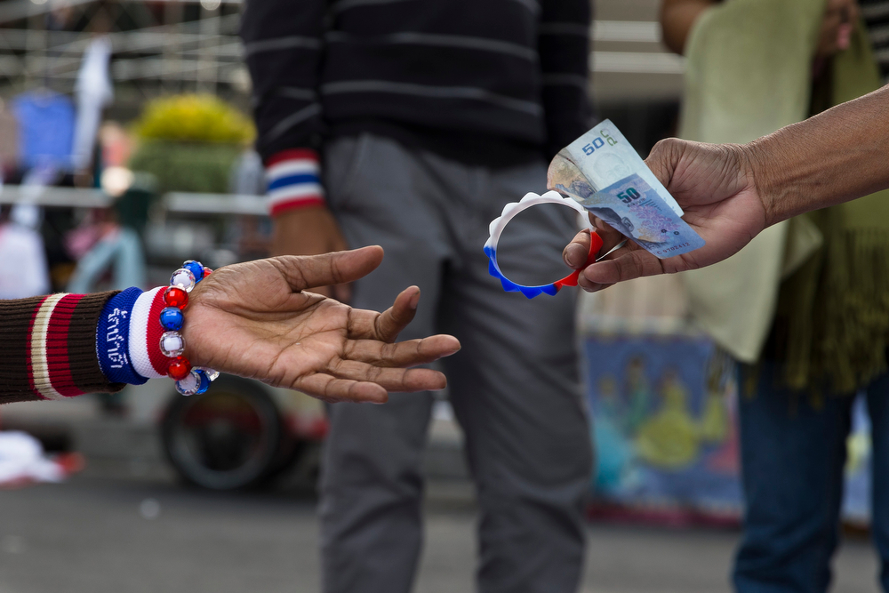 . An anti-government People\'s Democratic Reform Committee (PDRC) protester purchases a trinket from a street vendor at an encampment in the Pathumwan district of Bangkok Thursday, Jan. 16, 2014. Anti-government protesters were on the march again in the Thai capital Thursday, targeting government offices they have not previous interfered with to keep up pressure on Prime Minister Yingluck Shinawatra to resign and call off next month\'s election. (AP Photo/John Minchillo)