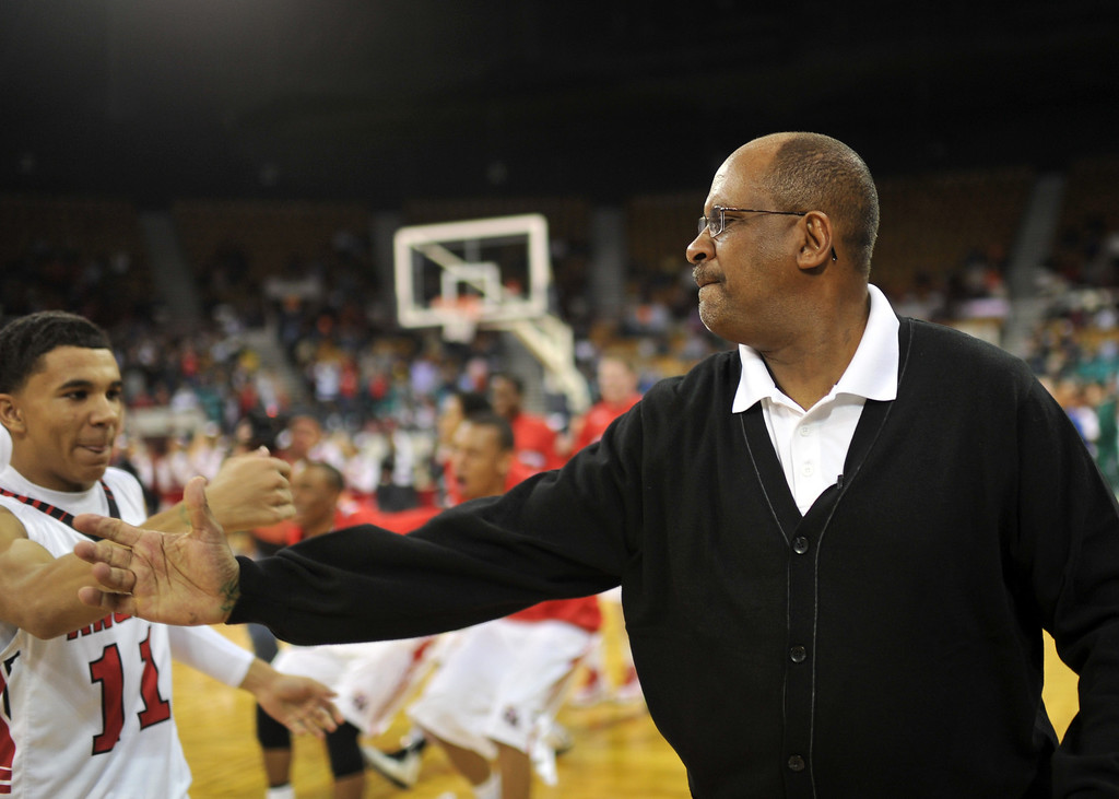 . DENVER, CO. - MARCH 08: Denver East High School boy\'s basketball team head coach Rudy Carey, right, celebrates his 700th win with Brian Carey #11 at Denver Coliseum. East High School won the 5A state quarter final game against Arapahoe High School by 60-55. March 8, 2013. Denver, Colorado. (Photo By Hyoung Chang/The Denver Post)