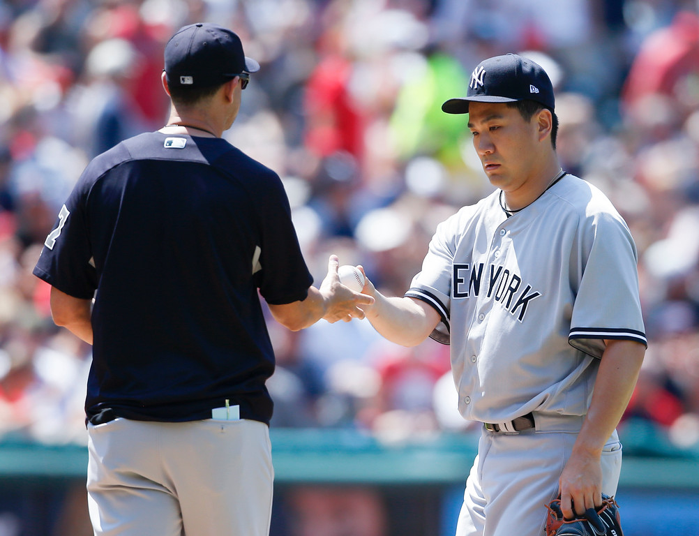 . New York Yankees manager Aaron Boone, left, removes Masahiro Tanaka from a baseball game against the Cleveland Indians during the seventh inning Sunday, July 15, 2018, in Cleveland. (AP Photo/Ron Schwane)