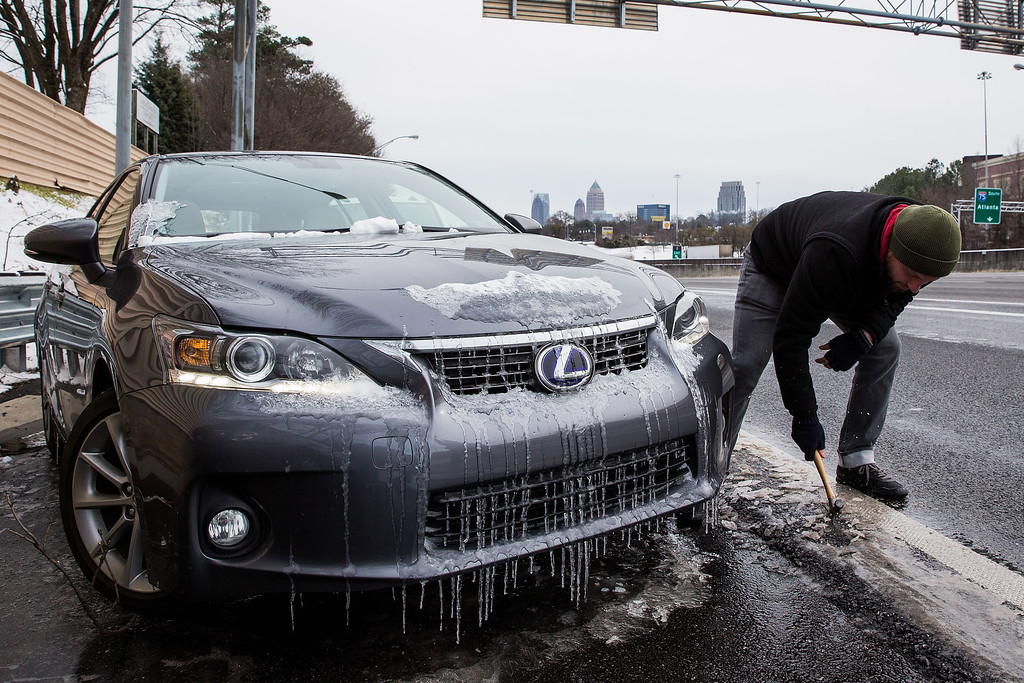 . Joe Galunas works to clear ice and retrieve the car he abandoned on an exit ramp along I-75 North during the winter storm January 29, 2014 in Atlanta, Georgia.    (Photo by Daniel Shirey/Getty Images)