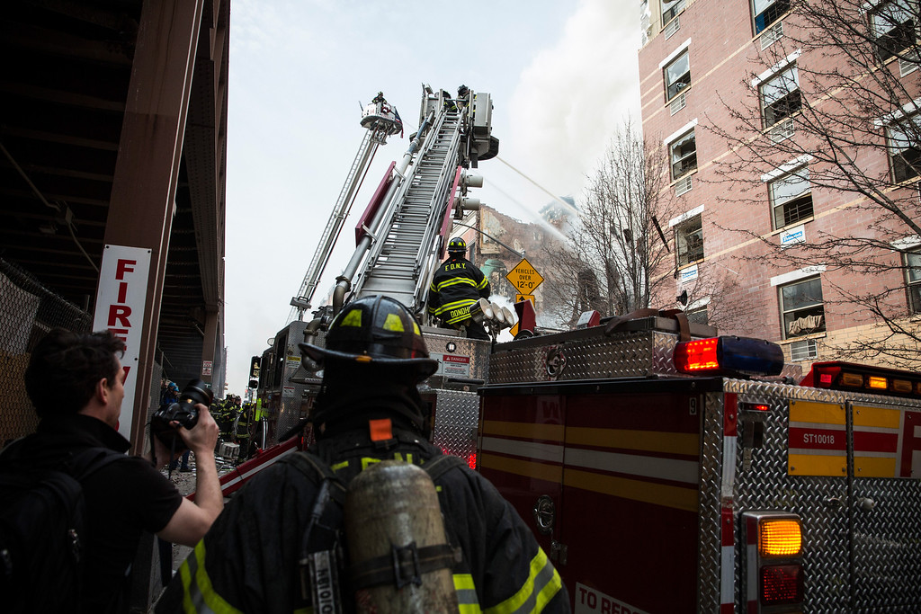 . A ladder truck pours water as the Fire Department of New York (FDNY) respond to a 5-alarm fire and building collapse at 1646 Park Ave in the Harlem neighborhood of Manhattan March 12, 2014 in New York City. Reports of an explosion were heard before the collapse of two multiple-dwelling buildings that left at least 11 injured.  (Photo by Andrew Burton/Getty Images)