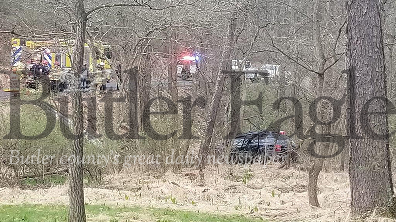 """Jim Smith photo. Emergency crews respond to a Tuesday morning crash on Pattison Street Extension in Jackson Township that police suspect was caused by a """"rolling domestic"""" and injured two people, a formerly married couple. The Jeep Grand Cherokee that Nichole M. Saeler, 46, of Summit Township, was driving, ended over an embankment and into a wooded area. She and her passenger, Joseph E. Saeler, 50, of Oakland Township, were both taken to hospitals with injuries."""