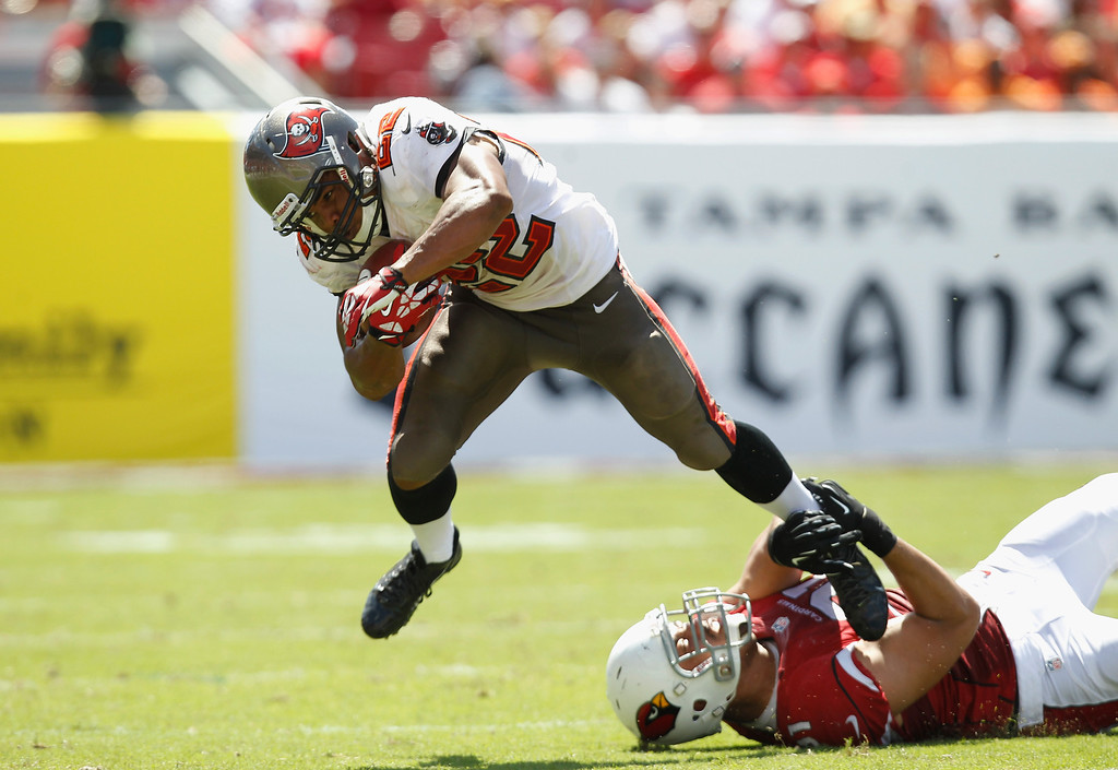 . TAMPA, FL - SEPTEMBER 29: Doug Martin #22 of the Tampa Bay Buccaneers gets tripped up against Matt Shaughnessy #91 of the Arizona Cardinals during the 2nd quarter at Raymond James Stadium on September 29, 2013 in Tampa, Florida.