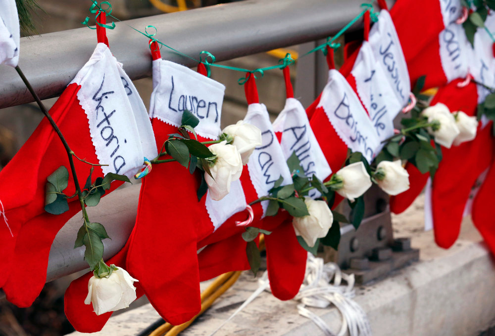 Description of . Christmas stockings with the names of shooting victims hang from railing near a makeshift memorial near the town Christmas tree in the Sandy Hook village of Newtown, Conn., Wednesday, Dec. 19, 2012. The memorial, which was put up in the aftermath of the elementary school shooting that shocked the small town, is increasing in size as the days go on. More funerals are scheduled for Wednesday, as the town continues to mourn its victims. The gunman, Adam Lanza, walked into Sandy Hook Elementary School in Newtown, Conn., Dec. 14, and opened fire, killing 26 people, including 20 children, before killing himself. (AP Photo/Julio Cortez)