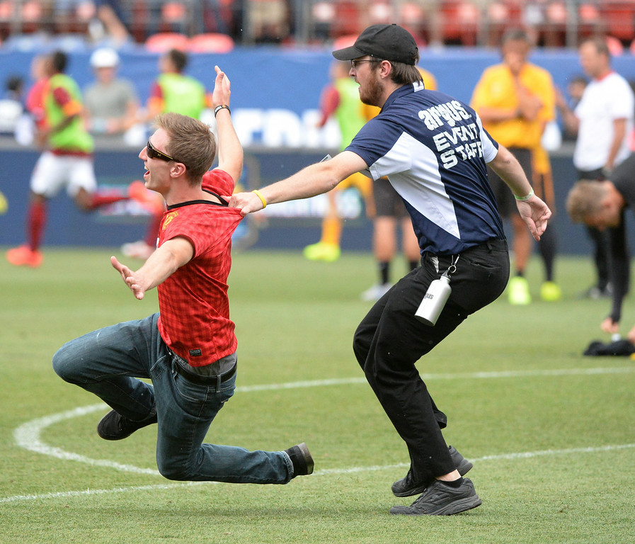 . A Manchester United fan was dragged down from behind by a security staffer at the end of the game. Manchester United defeated AS Roma 3-2 in an exhibition soccer game at Sports Authority Field in Denver Saturday afternoon, July 27, 2014. Photo by Karl Gehring/The Denver Post