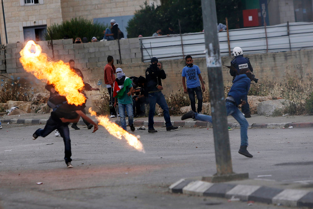 . A Palestinian protestor throws a Molotov cocktail towards Israeli security forces during clashes to mark Nakba Day near the West Bank city of Ramallah May 15, 2013. Palestinians clashed with Israeli forces in the occupied West Bank and at East Jerusalem on Wednesday during demonstrations to mark 65 years since what they call the Nakba (Catastrophe) when Israel\'s creation caused many to lose their homes and become refugees.   REUTERS/Mohamad Torokman