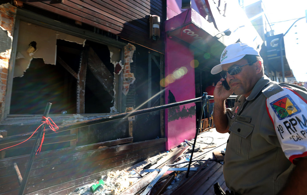 . A policeman checks the Kiss nightclub where a blaze on the eve killed more than 230 people, on January 28, 2012 in Santa Maria, southern Brazil. Brazilian police arrested four suspects --two of the Kiss club\'s owners, along with a pair of musicians who starred in the ill-fated pyrotechnic show, in the wake of the nightclub fire that forced sports officials to defend preparations for the World Cup and Olympics.    JEFFERSON BERNARDES/AFP/Getty Images