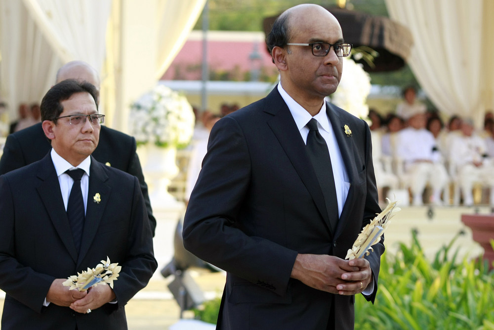 Description of . Tharman Shanmugaratnam (R), Singapore's deputy prime minister and minister for finance walks at the crematorium  to pray of the late former King Norodom Sihanouk minutes before his cremation, near the Royal Palace in Phnom Penh on February 4, 2013. Thousands of mourners massed in the Cambodian capital as the kingdom cremated its revered former King Norodom Sihanouk, who steered his country through six turbulent decades. AFP PHOTO/ KHEM SOVANNARA/AFP/Getty Images