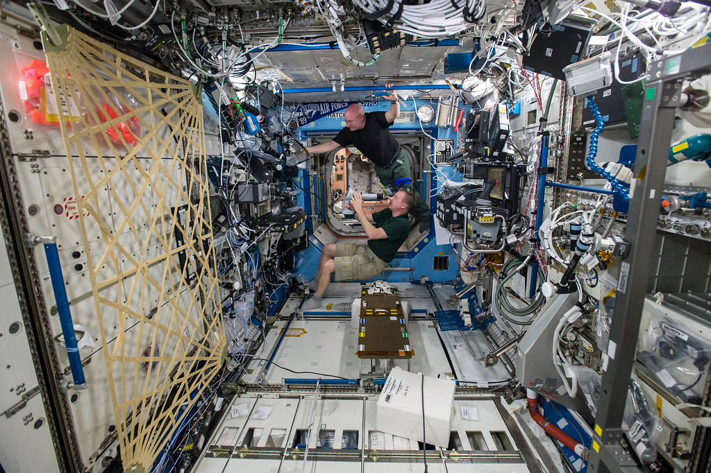 . In this April 9, 2015 photo made available by NASA, astronauts Terry Virts, bottom, and Scott Kelly perform eye exams in the Destiny Laboratory of the International Space Station as part of ongoing studies on vision health in microgravity. (NASA via AP)