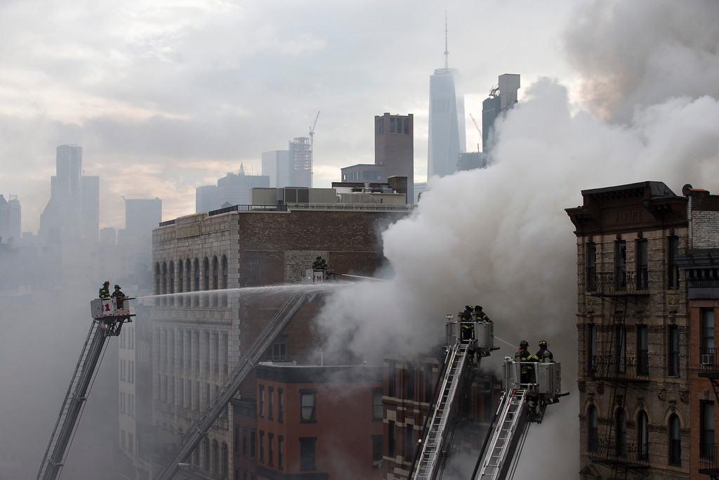 . New York City firefighters work the scene of a large fire and a partial building collapse in the East Village neighborhood of New York on Thursday, March 26, 2015. Orange flames and black smoke are billowing from the facade and roof of the building near several New York University buildings. (AP Photo/John Minchillo)