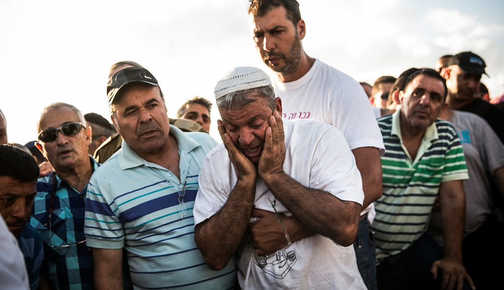 """. YAHUD MONOSON, ISRAEL - JULY 16:  Mourners weep for Dror Khenin during his funeral on July 16, 2014 in Yahud Monoson, Israel. Yesterday Khenin was the first Israeli to be killed by a Hamas mortar as he offered food to Israeli soldiers working near the Erez border crossing between Israel and Gaza. As Operation \""""Decisive Edge\"""" enters its ninth day, over 200 Palestinians have been killed in Israeli missile strikes.  (Photo by Andrew Burton/Getty Images)"""