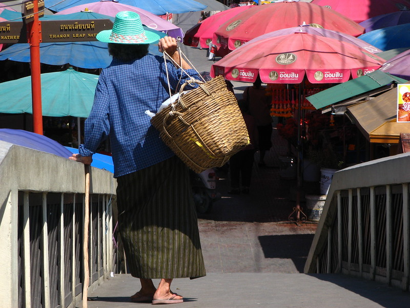 An older woman crossed the foot bridge to the fresh food market.