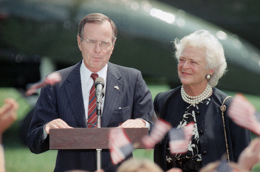 . President George H.W. Bush, left, and first lady Barbara Bush smile as well-wishers wave U.S. flags upon their arrival on the south lawn of the White House in Washington July 18, 1989. (AP Photo/Bob Daugherty)