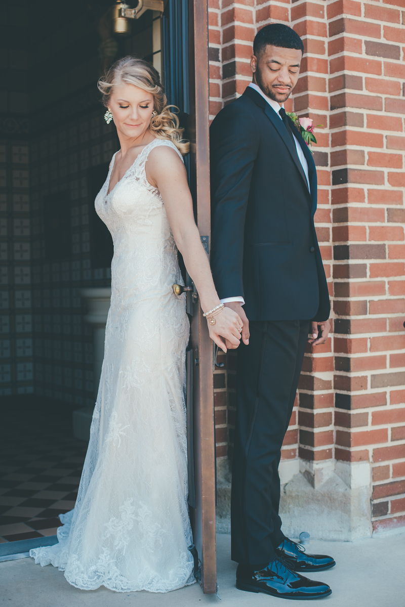 A bride and groom holding hands on different sides of a door just before their first look