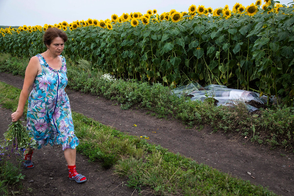 . A woman walks past a body covered with a plastic sheet near the site of a crashed Malaysia Airlines passenger plane near the village of Rozsypne, Ukraine, eastern Ukraine Friday, July 18, 2014. Rescue workers, policemen and even off-duty coal miners were combing a sprawling area in eastern Ukraine near the Russian border where the Malaysian plane ended up in burning pieces Thursday, killing all 298 aboard. (AP Photo/Dmitry Lovetsky)