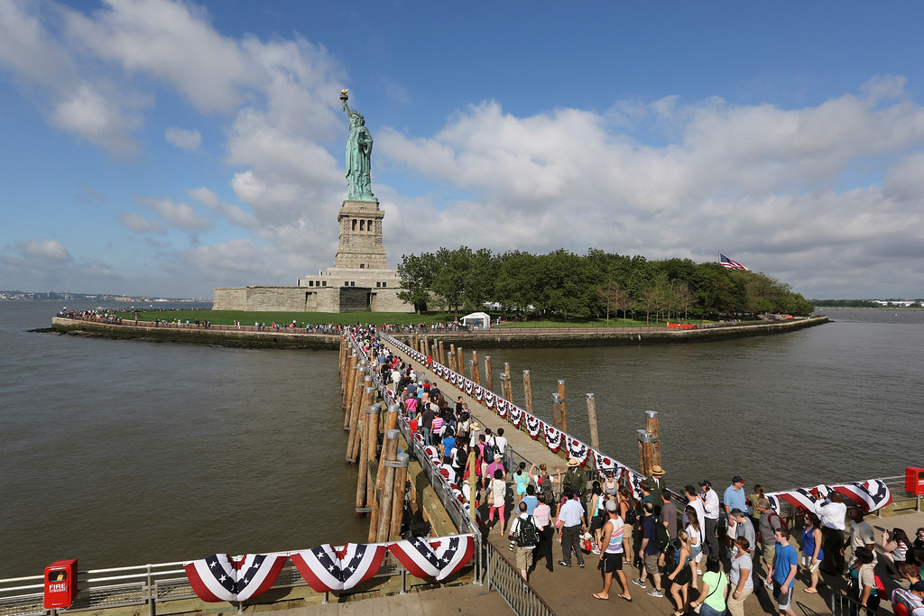 . Visitors to the Statue of Liberty disembark onto Liberty Island from the first ferry to leave Manhattan, Thursday, July 4, 2013, in New York. The Statue of Liberty finally reopened on the Fourth of July months after Superstorm Sandy swamped its little island in New York Harbor as Americans across the country marked the holiday with fireworks and barbecues. (AP Photo/Mary Altaffer)