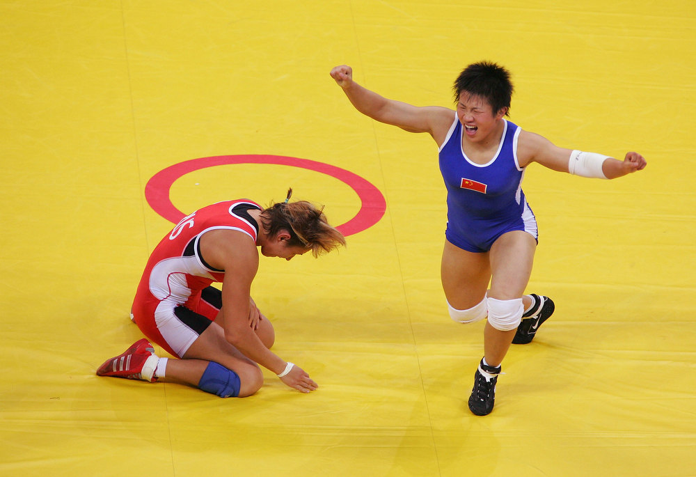 Description of . Xu Wang of China (blue) celebrates her win over Gouzel Maniourova of Russia in the women's Freestyle wrestling 72 kg gold medal match on August 23, 2004 during the Athens 2004 Summer Olympic Games at Ano Liossia Olympic Hall in Athens, Greece. (Photo by Al Bello/Getty Images)
