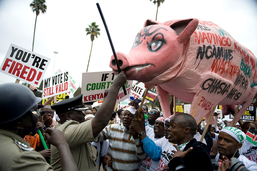 . Kenyan police attempt to intercept protestors carrying an effigy of a pig during a demonstration outside the parliament after lawmakers voted themselves hefty salary increases on June 11, 2013 in Nairobi. The protestors had intended to occupy the parliament but were not allowed in by anti-riot police. TONY KARUMBA/AFP/Getty Images