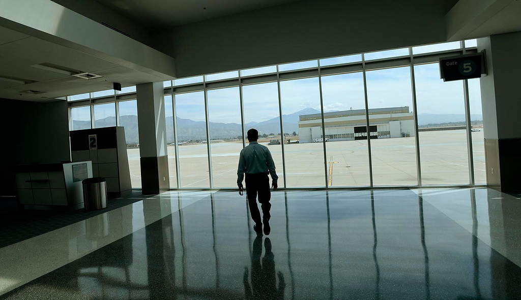 . Airport Manager Scott Gibbs walks towards a window overlooking the tarmac of the San Bernardino International Airport March 28, 2013.  Built on the former the site of the former Norton Air Force Base, is often described by local officials as one of the East Valley\'s best hopes for economic growth. Norton closed in 1994.  GABRIEL LUIS ACOSTA/STAFF PHOTOGRAPHER.