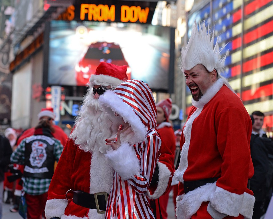 . People dressed as Santa Claus and Mrs. Claus pose for pictures in Times Square as they gather for the annual Santacon festivities on December 13, 2014 in New York. AFP PHOTO/DON EMMERT/AFP/Getty Images