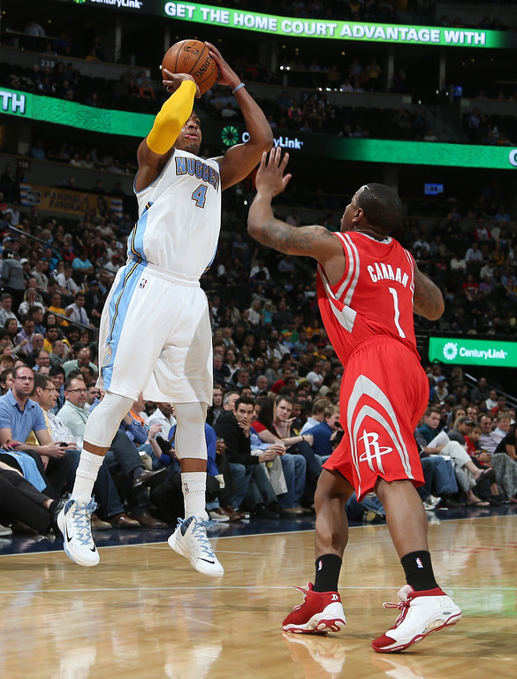 . Denver Nuggets guard Randy Foye, left, launches a three-point basket over Houston Rockets guard Isaiah Canaan in the third quarter of the Nuggets\' 123-116 victory in an NBA basketball game in Denver on Wednesday, April 9, 2014. (AP Photo/David Zalubowski)
