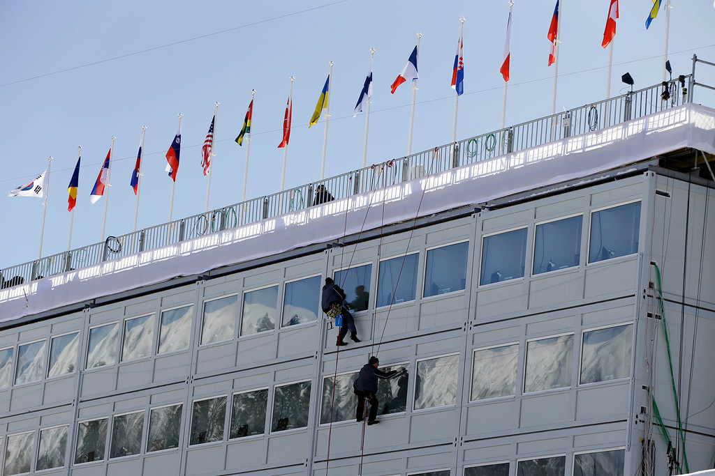 . Workers clean the windows of the Cross Country ski stadium, at the 2014 Winter Olympics, Tuesday, Feb. 4, 2014, in Krasnaya Polyana, Russia. (AP Photo/Kristy Wigglesworth)