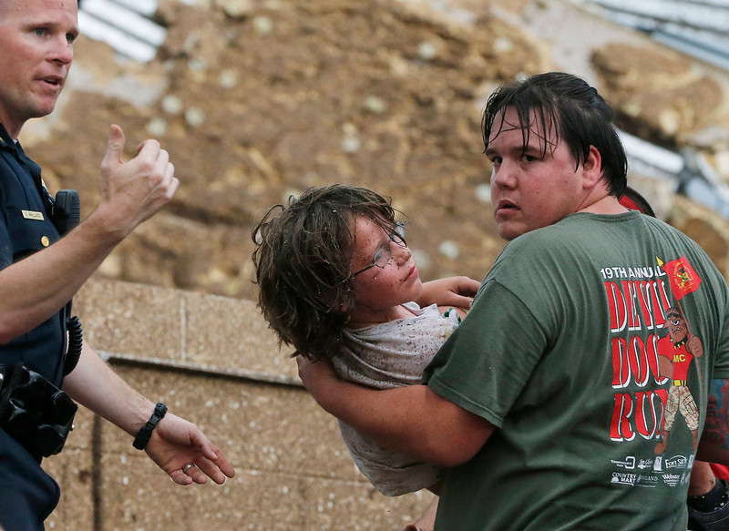 . A child is carried from the rubble of the Plaza Towers Elementary School following a tornado in Moore, Okla., Monday, May 20, 2013. A tornado as much as a mile (1.6 kilometers) wide with winds up to 200 mph (320 kph) roared through the Oklahoma City suburbs Monday, flattening entire neighborhoods, setting buildings on fire and landing a direct blow on an elementary school. (AP Photo/Sue Ogrocki)