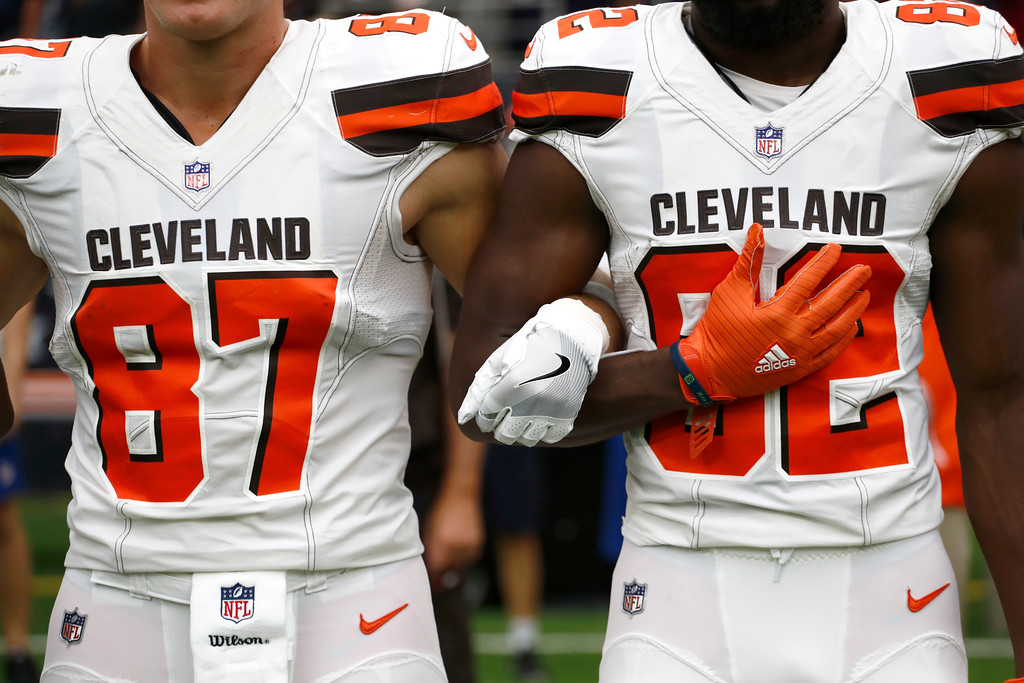 . Cleveland Browns\' Seth DeValve (87) and Kasen Williams (82) interlock arms during the playing of the national anthem before an NFL football game against the Houston Texans on Sunday, Oct. 15, 2017, in Houston. (AP Photo/Eric Gay)