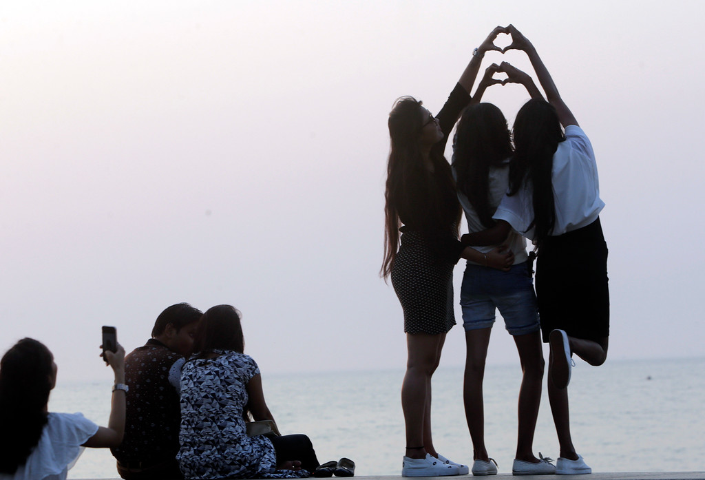 . Girls stand by the Arabian Sea promenade and form heart shapes with their hands on Valentine\'s Day in Mumbai, India, Tuesday, Feb 14, 2017. (AP Photo/Rajanish Kakade)