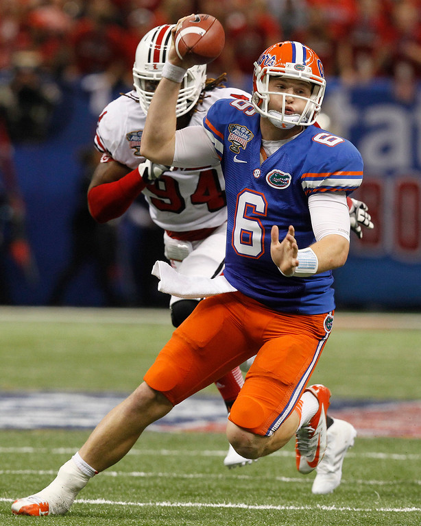 . Florida quarterback Jeff Driskel (6) is pursued by Louisville defensive end Lorenzo Mauldin (94) in the first half of the Sugar Bowl NCAA college football game Wednesday, Jan. 2, 2013, in New Orleans. (AP Photo/Butch Dill)