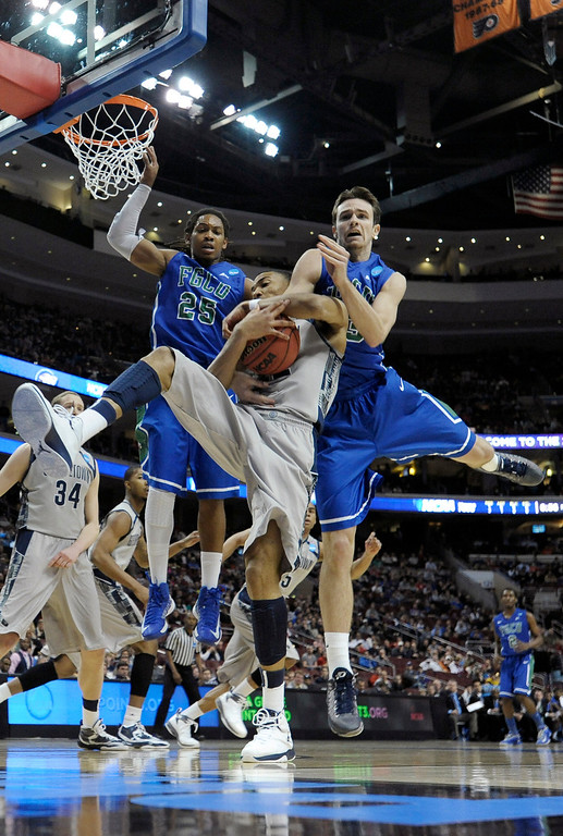 . Georgetown\'s Otto Porter Jr., center, pulls in a rebound against Florida Gulf Coast\'s Sherwood Brown, left, and Eddie Murray during the first half of a second-round game of the NCAA college basketball tournament, Friday, March 22, 2013, in Philadelphia. (AP Photo/Michael Perez)