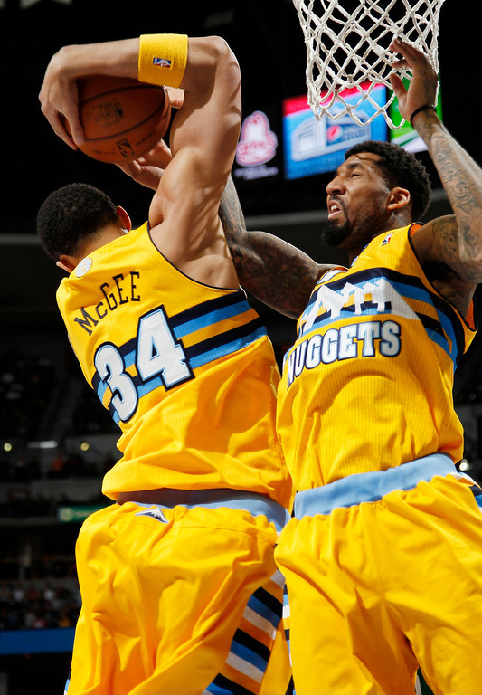 . Denver Nuggets forwards JaVale McGee, left, and Wilson Chandler get tied up with each other on a rebound, against the Boston Celtics in the first quarter of an NBA basketball game in Denver on Tuesday, Feb. 19, 2013. (AP Photo/David Zalubowski)